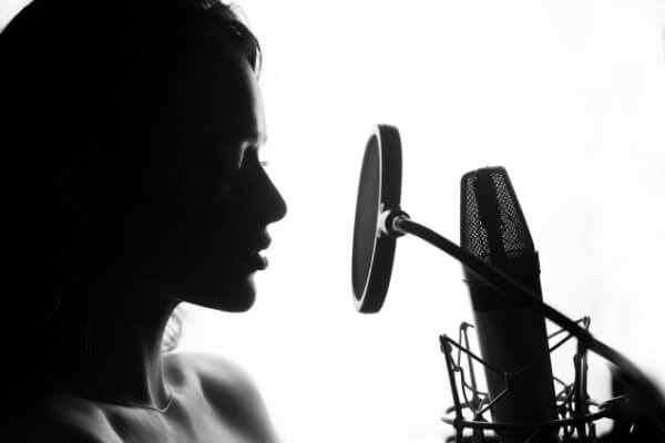chica rapera grabando freestyle rap con micrófono de condensador