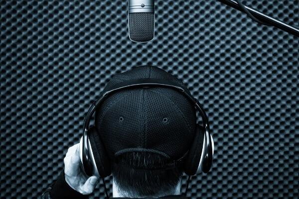 Chico rapero grabando freestyle rap con micrófono de condensador elevado