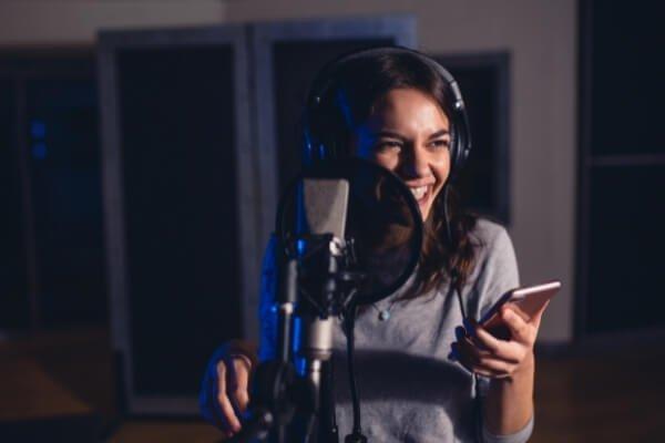 chica junto a microfono de grabación